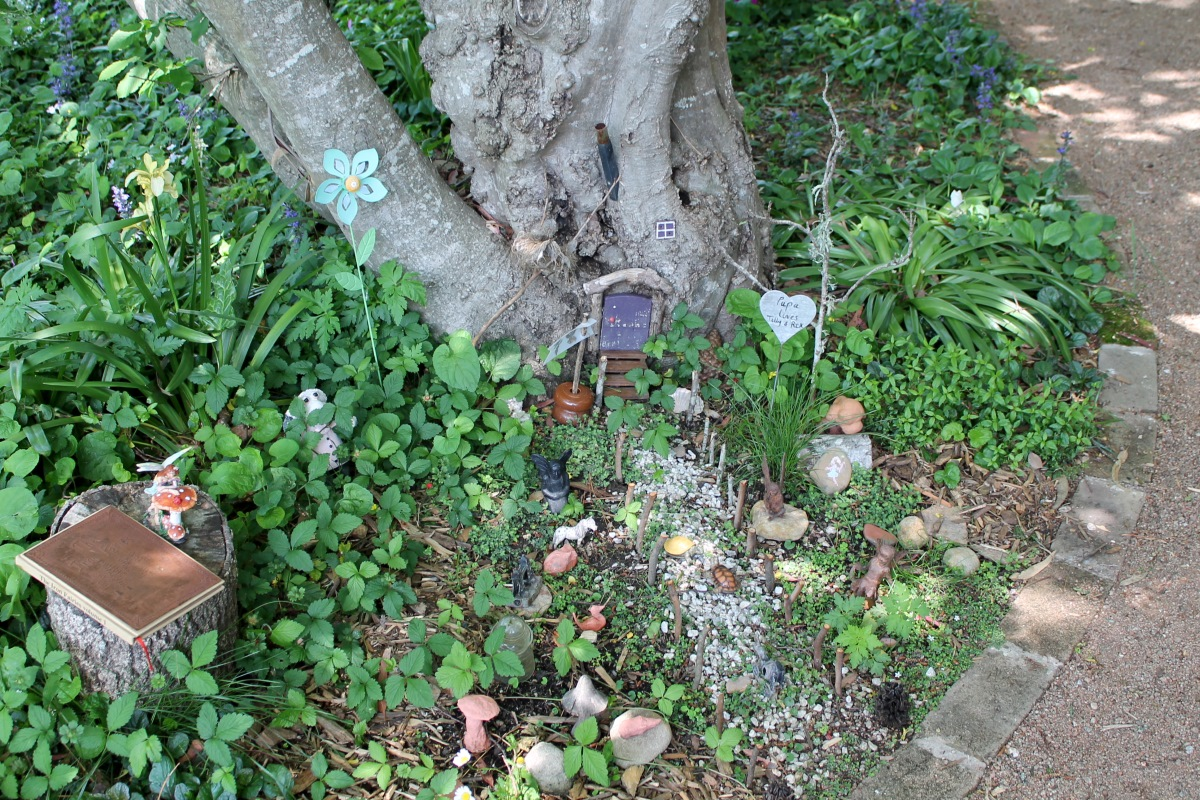 A fairy garden at the base of a tree.
